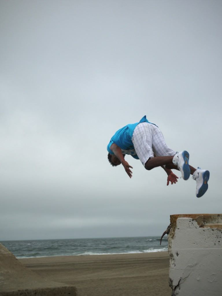 Young guy leaping the sea-wall at Ocean Beach, San Francisco